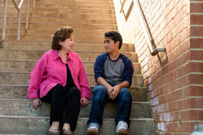 CASA Volunteer and child sitting on steps outside. CASA Volunteer is a middle aged caucasian woman wearing a pink blazer. Child is around ten years old, has a medium skin tone, and is wearing his dark hair short, and also wearing a navy blue and grey baseball tshirt.