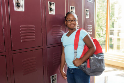 Teenage African American girl leaning against red lockers at school. Girl is wearing glasses, a blue t shirt, and has her hair in a protective style.